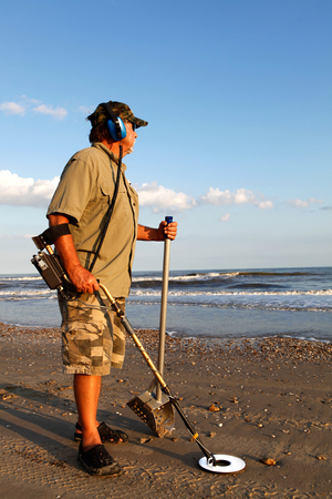 detecting: Man metal detecting on the beach