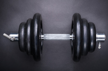 dumbbell with typesetting discs weighting on dark background