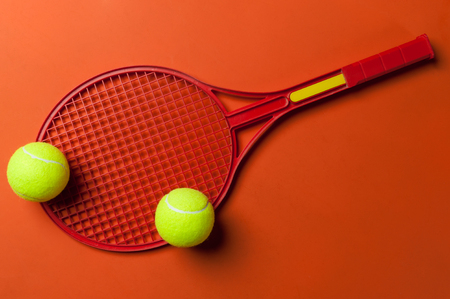 tennis racket and ball on red background Stock Photo