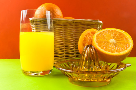 manual juicer with oranges on colored background