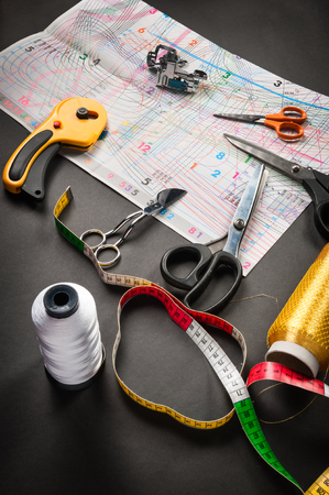 sewing tools thread with scissors and measuring tape on dark