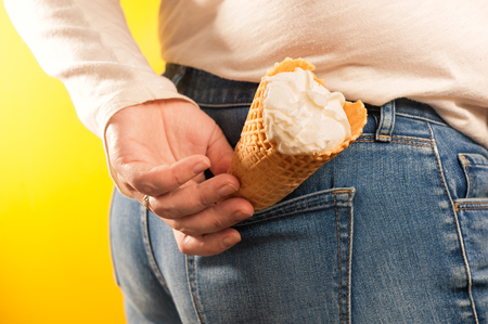 ice cream cone in jeans pocket on yellow background