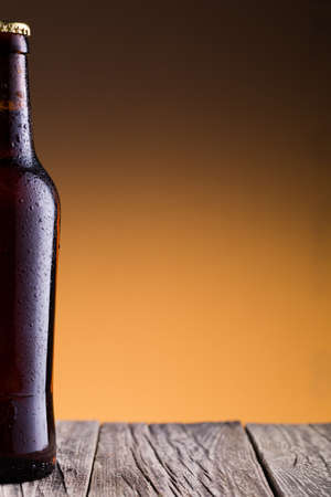 condensate: Beer bottle with water drops on a wooden table Stock Photo