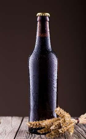 spica: Botella de cerveza con la espiga en una mesa de madera Foto de archivo