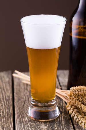spica: Botella de cerveza con un vaso y espiga en un fondo marr�n Foto de archivo