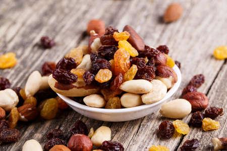 frutas secas: Nueces mixtas en un plato sobre fondo de madera. Foto de archivo