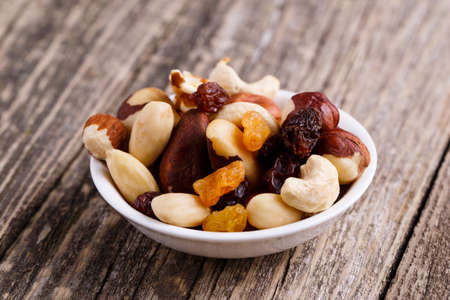 mixed nuts: Mixed nuts on a plate on wooden background.
