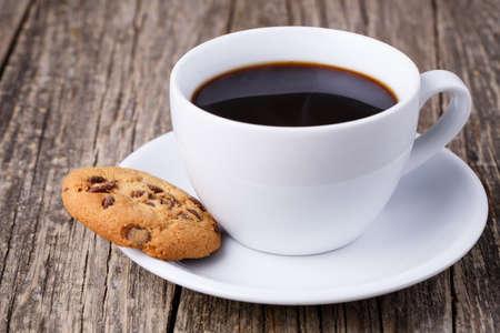 Kopje koffie met koekjes op een tafel.