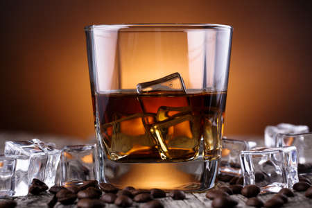 table glass: Alcohol on a wooden table with coffee beans. Stock Photo