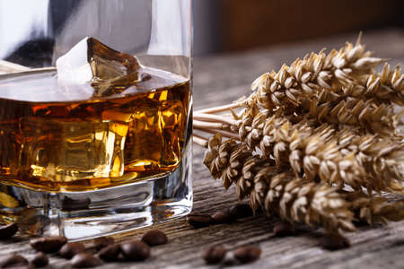 Alcohol with ice and wheat on a wooden table. photo