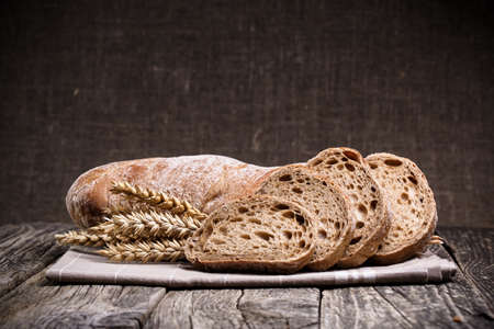 Slices of bread with rye on a wooden background. Archivio Fotografico