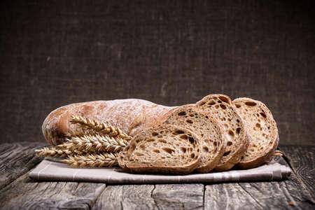comiendo pan: Rebanadas de pan con centeno en un fondo de madera.