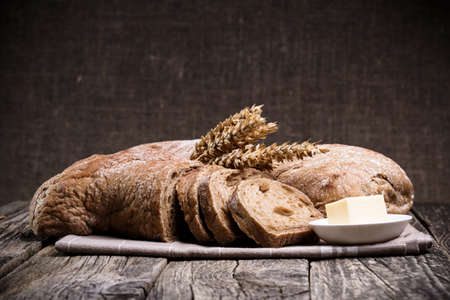 Slices of bread with rye on a wooden background. photo