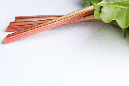 Bundle of rhubarb on white wooden table. photo