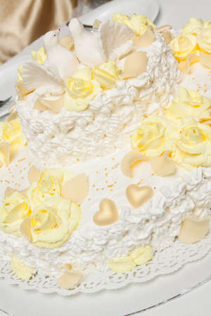 lace doily: Delicious wedding cake with roses on lace doily.