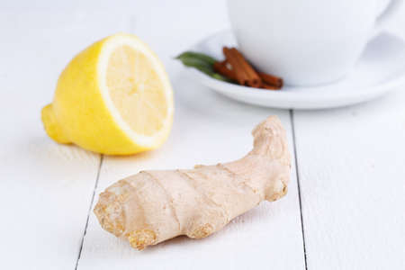 Fresh ginger with lemon  on white wooden table. photo