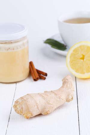 Fresh ginger with cinnamon, honey jar, and green tea. photo