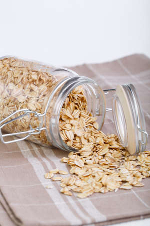 spilling: Oat flakes spilling out of glass jar. Stock Photo