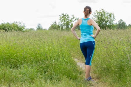 stays: Young woman in running suit stays outdoor.