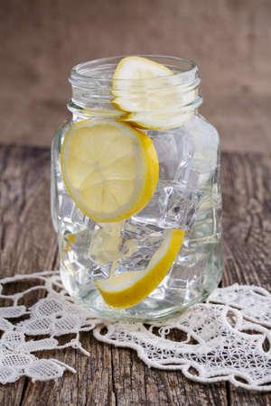 vasos de agua: Frasco de vidrio con lim�n y hielo en la mesa de madera.