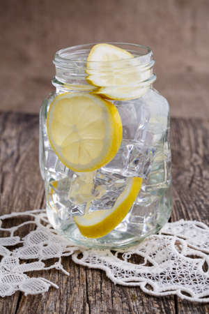 Glass jar with lemon and ice on wooden table.
