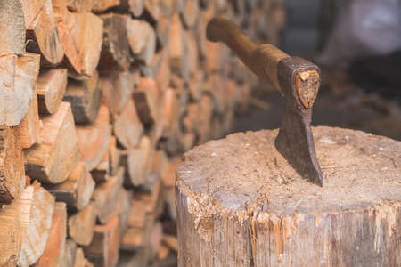 Ņhatchet: Hatchet thrusted in old stump with background of logs. Stock Photo