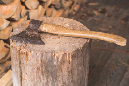 hatchet: Hatchet thrusted in old stump with background of logs. Stock Photo