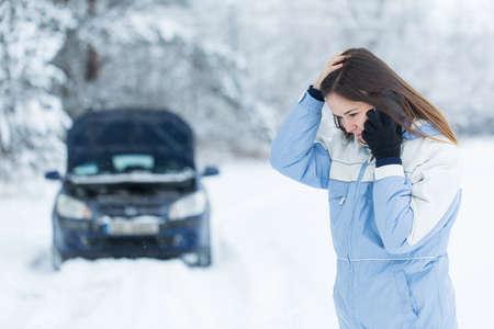 Winter auto verdeling - vrouw oproep voor hulp. Stockfoto