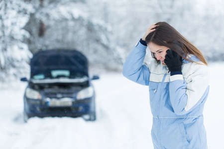 Winter car breakdown - woman call for help.