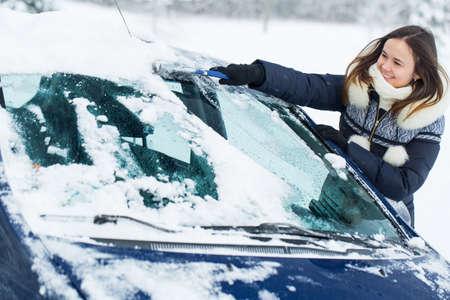 Femme enlever la neige du pare-brise avec une brosse à neige.