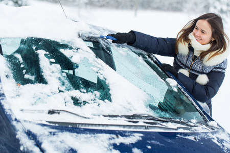 Woman remove snow from windshield with snow brush.