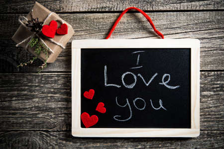 about you: I love you handwritten on black chalkboard with gift box.