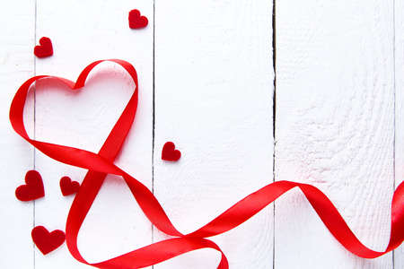 Red ribbon heart on white wooden background on valentines day.