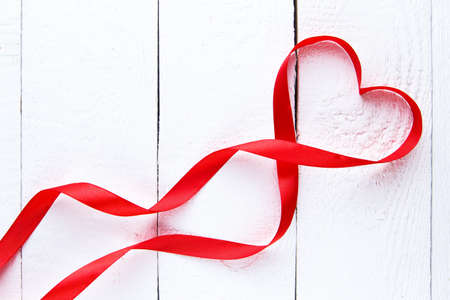ribbon heart: Red ribbon heart on white wooden background on valentines day.