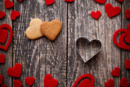 galletas de jengibre: Heart shape ginger cookies on wooden table on valentines day.
