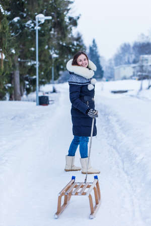 winter fun: Winter fun of young woman walking with sleds.