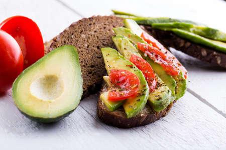 rye bread: Avocado sandwich with tomato and seasoning on dark rye bread. Stock Photo