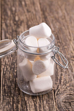 marshmellow: Marshmallows in a glass jar on wooden table.