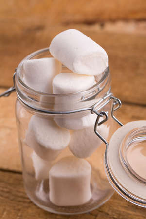 marshmellow: Sweet marshmallows in a glass jar on wooden table.