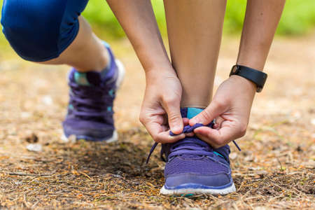 shoe laces: Running shoes - woman tying shoe laces. Close up of female legs in forest trail. Stock Photo