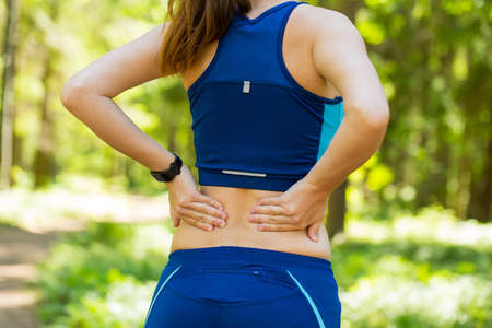 Close up athletic woman with smartwatches holding her painful injured back while doing an exercise.