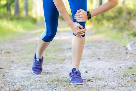 injured knee: Woman runner hold her sports injured knee. Stock Photo