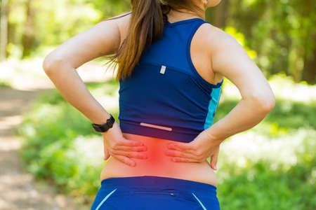 accident rate: Close up athletic woman with smartwatches holding her painful injured back while doing an exercise.