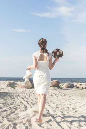 Bride with wedding bouquet go to the sea.