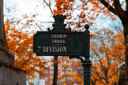 An old road sign in the most famous cemetery of Paris Pere Lachaise, France. Tombs of various famous people. Golden autumn over eldest tombs