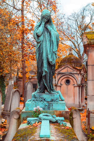 Old stone woman monument in the most famous cemetery of Paris Pere Lachaise, France. Tombs of various famous people. Golden autumn over eldest tombs