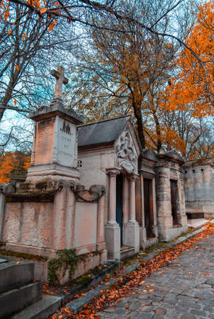 A view on autumn alley of the most famous cemetery of Paris Pere Lachaise, France. Tombs of various famous people. Golden autumn over eldest tombs