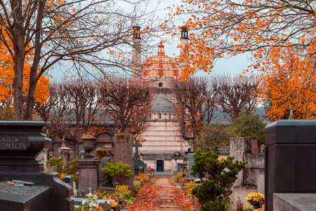 A view on autumn alley of the most famous cemetery of Paris Pere Lachaise, France. The Crematorium on the background. Tombs of various famous people. Golden autumn over eldest tombs Publikacyjne