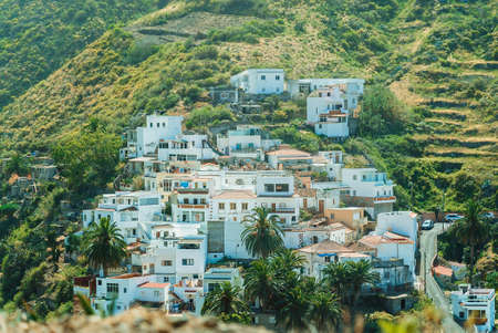 Bright white small buildings on a mountain hill among the green vegetation on a sunny day. Colorful scenic mountain village Taganana on Tenerife Island, Canary Islands, Spain.