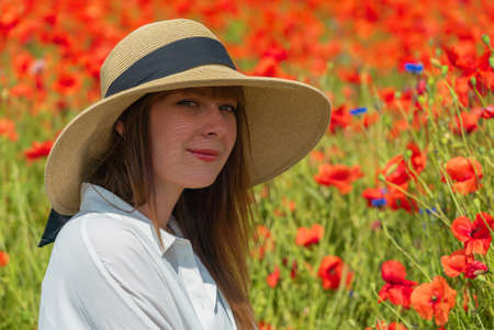Young girl in the white dress and hat sitting in the poppy field. Portrait of woman outdoors